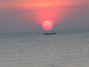 perahu nelayan melintas tepat di bawah matahari senja Takisung