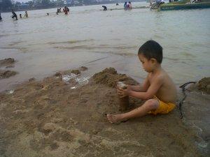 Anak kecil bermain di pinggir Pantai Tayan